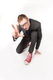 Jeune homme dans une jupe grise et des espadrilles rouges Images libres de droits