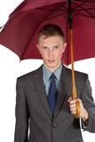Jeune homme dans une jupe grise et des espadrilles rouges sur un fond blanc Photos stock