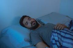 Jeune homme de barbe se trouvant sur le lit éveillé images stock