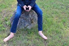 Jeune homme de barefeet avec le téléphone photo libre de droits