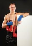 Jeune homme de boxeur tenant le conseil proche, d'isolement dessus Images stock