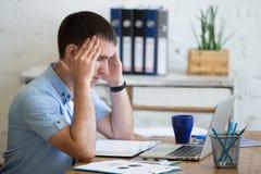 Jeune homme de bureau souffrant du mal de tête images stock