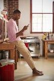 Jeune homme de couleur à l'aide du smartphone dans la cuisine, intégrale Image stock