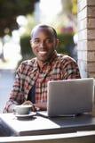 Jeune homme de couleur avec l'ordinateur portable en dehors d'un café regardant à l'appareil-photo image libre de droits