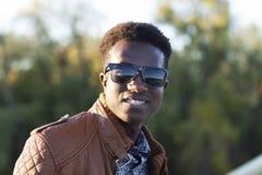 Jeune homme de couleur beau dans les lunettes de soleil et une veste en cuir sur a Photos stock