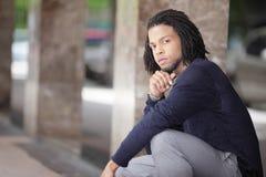 Jeune homme de couleur dans une pose d'accroupissement Photo libre de droits