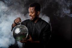 Jeune homme de couleur frais avec la bille de disco au-dessus du fond noir images stock