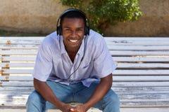 Jeune homme de couleur heureux s'asseyant sur le banc de parc avec des écouteurs Photo libre de droits