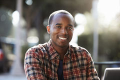Jeune homme de couleur s'asseyant dehors, portrait photo stock