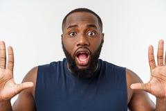 Jeune homme de couleur de sport au-dessus d'une surprise même de fond gris images stock