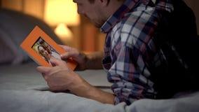 Jeune homme de désespoir se trouvant sur le lit regardant la photo avec l'amie, tristesse image stock