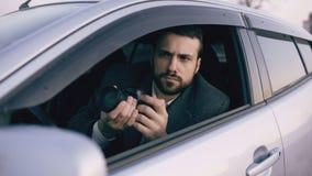 Jeune homme de détective privé s'asseyant à l'intérieur de la voiture et photographiant avec l'appareil-photo de dslr Images libres de droits