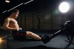 Jeune homme de forme physique à l'aide de la machine à ramer dans le gymnase images stock