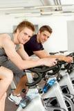 Jeune homme de forme physique sur la rotation de vélo de gymnastique Photo stock