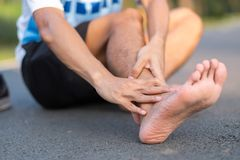 Jeune homme de forme physique tenant sa blessure à la jambe de sports muscle douloureux pendant la formation Coureur asiatique ay photo stock