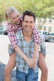 Jeune homme de hanche donnant à son amie blonde un ferroutage Image libre de droits