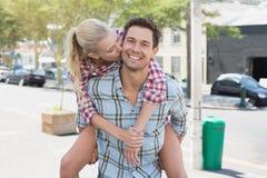 Jeune homme de hanche donnant à son amie blonde un ferroutage Images stock