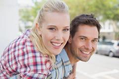 Jeune homme de hanche donnant à son amie blonde un ferroutage Photo libre de droits