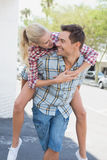 Jeune homme de hanche donnant à son amie blonde un ferroutage Photographie stock libre de droits