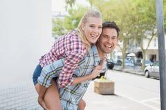 Jeune homme de hanche donnant à son amie blonde un ferroutage Photos libres de droits