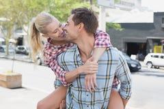 Jeune homme de hanche donnant à son amie blonde un ferroutage Image stock