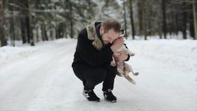 Jeune homme de Happyattractive dans coathaving noir avec un son chien de briquet dans un jour d'hiver Amitié, animal familier et  clips vidéos