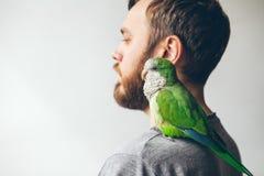Jeune homme de hippie de barbe à la maison avec son animal familier préféré sur l'épaule - perroquet vert de moine Photos libres de droits