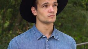Jeune homme de hippie dans le chapeau riant, décontracté devant l'appareil-photo banque de vidéos