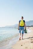 Jeune homme de hippie marchant le long du bord de mer et de la plage nu-pieds avec ses espadrilles à disposition Photographie stock