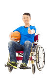 Jeune homme de l'Asie s'asseyant sur un fauteuil roulant et un pouce  Image libre de droits