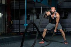 Jeune homme de lutte de cordes à l'exercice de séance d'entraînement de gymnase Photos stock