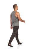Jeune homme de marche dans la vue arrière de survêtement de sport de Camo Photo stock