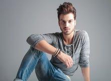 Jeune homme de mode détendant son bras sur son genou Photos stock