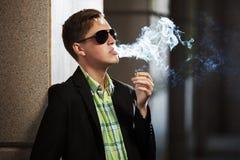 Jeune homme de mode dans des lunettes de soleil fumant une cigarette Photographie stock libre de droits