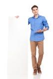 Jeune homme de mode présent un conseil blanc photo stock