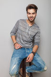 Jeune homme de mode s'asseyant sur un tabouret, souriant Images libres de droits