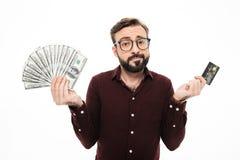 Jeune homme de pensée confus tenant la carte de crédit d'argent et Photos libres de droits