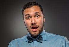 Jeune homme de portrait dans la chemise bleue, regardant avec la stupéfaction photographie stock