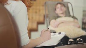 Jeune homme de portrait s'asseyant sur un berceau dans le bureau d'un psychologue, lui indiquant au sujet de ses problèmes jugean banque de vidéos