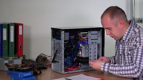 Jeune homme de réparateur installant l'unité de disque dur sur la caisse de PC de bureau au centre de calcul banque de vidéos