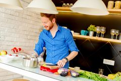 Jeune homme de Redhair faisant cuire la nourriture Photographie stock libre de droits