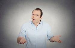 Jeune homme de regard drôle naïf muet, bras demandant quel est le problème photographie stock libre de droits