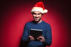 Jeune homme de Santa tenant un ordinateur de protection de comprimé Images libres de droits