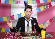 Jeune homme de soufflement un gâteau de chocolat de réception de vacances Images stock