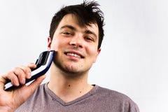 Jeune homme de sourire à l'aide du rasoir électrique devant le miroir Beauté, toilettage et concept de personnes Homme bel à l'ai photographie stock libre de droits