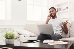 Jeune homme de sourire à la maison avec l'ordinateur portable et le mobile Photographie stock