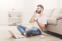 Jeune homme de sourire à la maison avec l'ordinateur portable et le mobile Image stock