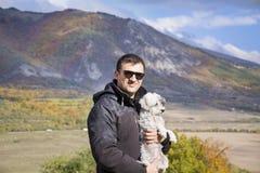 Jeune homme de sourire étreignant son petit chien blanc dans la montagne d'automne Image libre de droits