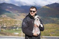 Jeune homme de sourire étreignant son petit chien blanc dans la montagne d'automne Photo libre de droits