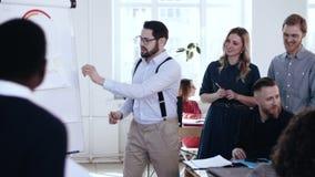 Jeune homme de sourire actif heureux d'entraîneur de finances menant la discussion active avec l'équipe diverse lors de la réunio banque de vidéos